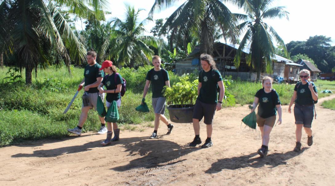 Voluntarios llevando materiales a la granja durante su voluntariado de conservación en Perú.